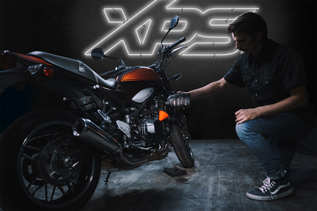 Man maintaining his motorbike with XPS oil