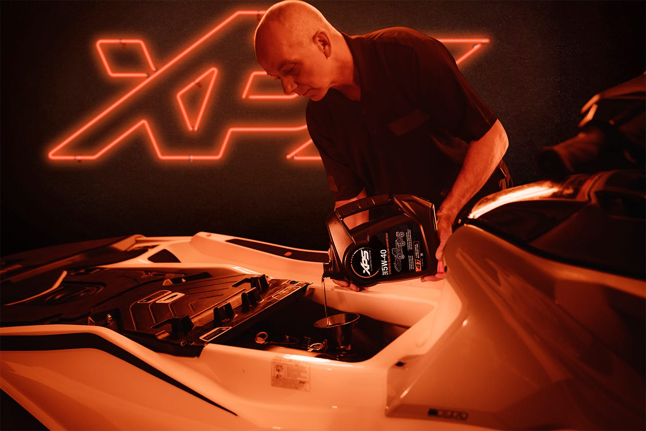 Man adding XPS 5W-40 oil to his Personal Watercraft